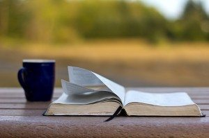 Bible on a picnic table with the wind turning the pages and a coffee mug.